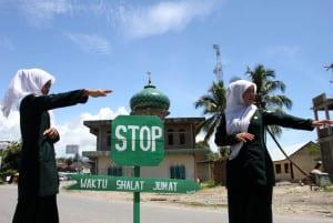 Polisi Syariat (Wilayathul Hisbah) wanita menjaga persimpangan dan mengalihkan jalur lalu lintas di kawasan yang berdekatan dengan masjid saat pelaksanaan ibadah shalat Jumat di Desa Meudang Ara, Blangpidie, Aceh Barat Daya, NAD, Jumat (25/10). Anggota wilayathul Hisbah (WH) wanita setiap pelaksanaan ibadah jumat ditugaskan untuk menjaga ketenangan beribadah umat muslim sebagai realisasi qanun nomor 11/2002 tentang aqidah, ibadah dan syiar islam. ANTARA FOTO/Irwansyah Putra/ed/pd/13.